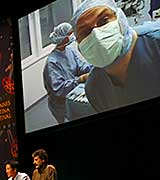 Surgeon on screen above stage at meeting